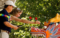 A woman paints a traditional dragon head during the Charlotte Dragonboat Association racing on Lake Norman in NC. ,