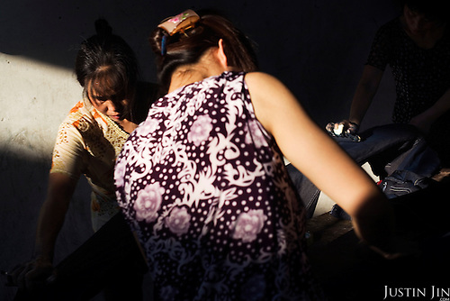 """Workers scrub jeans to create a worn-out look in Zhongshan city, China. .This picture is part of a photo and text story on blue jeans production in China by Justin Jin. .China, the """"factory of the world"""", is now also the major producer for blue jeans. To meet production demand, thousands of workers sweat through the night scrubbing, spraying and tearing trousers to create their rugged look. .At dawn, workers bundle the garment off to another factory for packaging and shipping around the world..The workers are among the 200 million migrant labourers criss-crossing China.looking for a better life, at the same time building their country into a.mighty industrial power."""