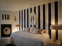 A guest bedroom has been decorated in striking Regency-style black and white stripe