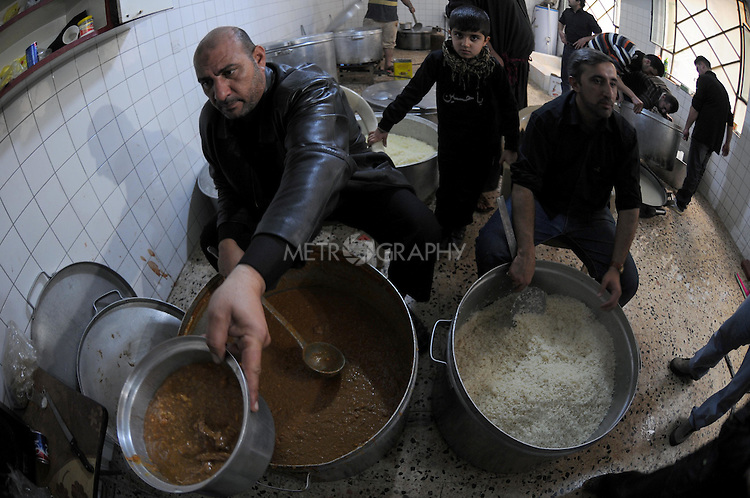IRAQ, SULAIMANIYAH:  Men hand out traditional food for free as part of the Ashura holiday...Around 500 hundred worshipers, many of them internally displaced Arabs, celebrated the Shia holiday of Ashura--the mourning of the death of the grandson of the Islamic prophet Mohammed.  ..Photo by Kamaran Najm/Metrography