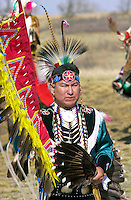 A CANADIAN PLAINS INDIAN IN TRADITIONAL COSTUME WEARING A FEATHER HEAD-DRESS AND CARRYING A FEATHER FAN AT WANUSKEWIN HERITAGE PARK, SASKATOON, CANADA.