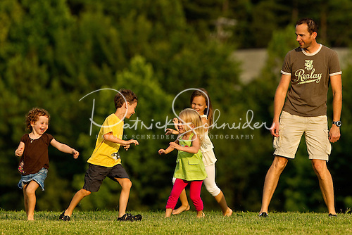 Photo of children playing tag at the McGuire energy station summer pops concert. Image is not model released.
