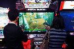 People playing Razing Storm shooting video game arcade slot machines in Tokyo, Japan