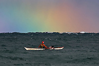 A rainbow appears over a sea kayaker surfing waves on a rough Lake Superior near Marquette Michigan.