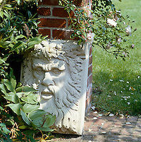 Sandstone sculpture relief propped up against a wall partly hidden by foliage