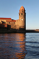 Bell tower, Eglise Notre Dame des Anges, Collioure, France, seen from the sea in which it is reflected. The bell tower was converted from a medieval lighthouse and the Mediterranean Gothic style nave was built in 1684. The dome was added to the bell tower in 1810. Picasso, Matisse, Derain, Dufy, Chagall, Marquet, and many others immortalized the small Catalan harbour in their works. Picture by Manuel Cohen.