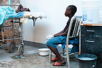 A boy watches over his father, who is sick with cholera, at the Hospital Albert Schweitzer on Friday, October 29, 2010 in Deschapelles, Haiti.