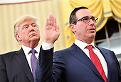United States President Donald Trump looks over the shoulder of Treasury Secretary Steven Munchin as he is sworn-in during a ceremony at the White House in Washington, D.C. on February 13, 2017. Mnuchin was confirmed by the Senate 54-47 earlier today. <br /> Credit: Kevin Dietsch / Pool via CNP