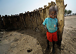 A child stands in front of the wall of a burned hut in Leu, a village in the contested Abyei region along the border between Sudan and South Sudan. The village was looted and burned in 2011 when soldiers and militias from the northern Republic of Sudan swept through the area, chasing out more than 100,000 Dinka Ngok residents. A few thousand families have returned to the region since northern combatants withdrew in 2012, yet their life is precarious. In Leu, the Catholic Church rehabilitated a clinic and drilled a well. For political and logistical reasons, the Catholic Church is one of the few organizations willing to openly accompany the people of Abyei during these uncertain times.