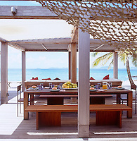 The outdoor dining area on a terrace overlooking the bay is shaded by a wooden pergola slung with a sailcloth to protect the furniture from the sun