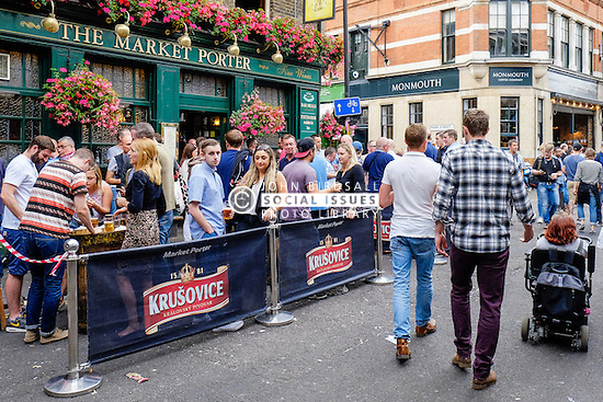 People drinking outside The Market Porter pub in Borough market, London.
