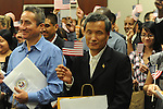 Braulio Ramon (left) and Shengkun Wen wave U.S. flags after becoming United States citizens during a naturalization ceremony in federal court in Oxford, Miss. on Friday, June 29, 2012. Forty seven persons took the oath of citizenship. (AP Photo/Oxford Eagle, Bruce Newman)