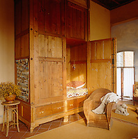 In this bedroom the cosy antique box bed is constructed from golden-brown pine