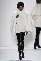 Model walks runway in an ivory saga royal fox mini coat lined with french lace, and ivory handloomed cashmere/silk tunic w/beaded T-Medallion+velvet leggings, from the Zang Toi Fall 2012 &quot;Glamour At Gstaad&quot; collection, during Mercedes-Benz Fashion Week New York Fall 2012 at Lincoln Center.