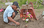 A man writes in the dirt at the grave of his wife and daughter who were killed during the November 2013 passage of Typhoon Haiyan and buried in a church yard in the city of Palo, in the Philippines province of Leyte. The storm was known locally as Yolanda.