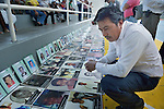 A local resident squats to examine dozens of photos laid out on the ground in Puerto Madero, Mexico, on December 17, 2013. The photos were brought by a caravan of Central Americans, mostly mothers looking for their disappeared or trafficked children, who came to Mexico for 17 days.