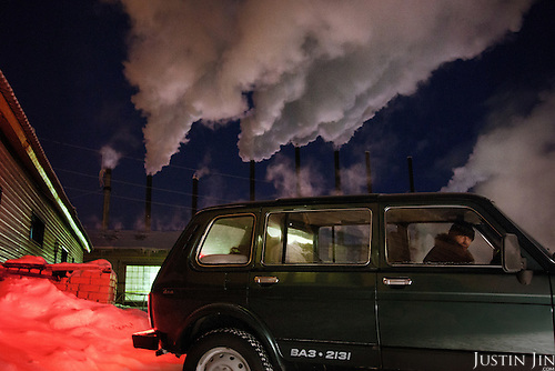 A car drives past a water-heating plant in Naryan-Mar, capital of the resource-rich Nenets Autonomous Region in Arctic Russia, where many of the oil and gas exploration companies have their local headquarters.