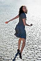 Woman running down cobblestone street, rear view