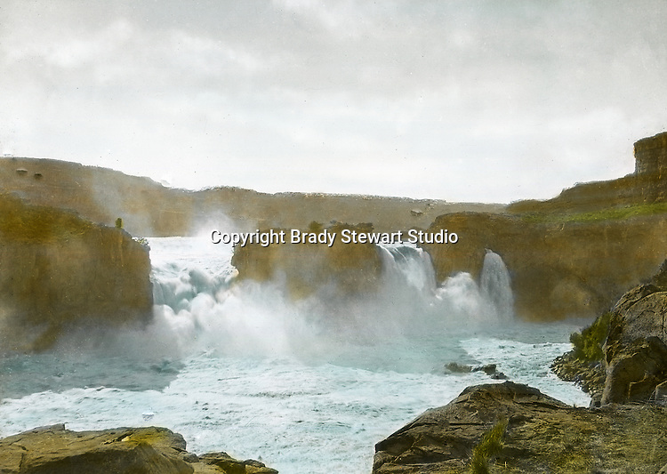 Twin Falls ID:  Named after the city with the same name, the water falls 125ft into the Snake River - 1910.   Brady Stewart and three friends went to Idaho on a lark from 1909 thru early 1912.  As part of the Mondell Homestead Act, they received a grant of 160 acres north of the Snake River.  Brady Stewart photographed the adventures of farming along with the spectacular landscapes. To give family and friends a better feel for the adventure, he hand-color black and white negatives into full-color 3x4 lantern slides.  The Process:  He contacted a negative with another negative to create a positive slide.  He then selected a fine brush and colors and meticulously created full color slides.