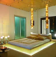 Low Japanese-style bed floating on a sea of light with a pair of tubular lights suspended from the ceiling