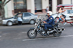 Havana, Cuba; a Cuban police officer driving down the Paseo de Marti on a motorcycle during morning rush hour