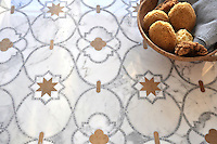 Vittoria, waterjet and hand cut mosaic shown in Lagos Gold honed, Calacatta Tia and Allure polished is part of the Miraflores Collection by Paul Schatz for New Ravenna Mosaics.