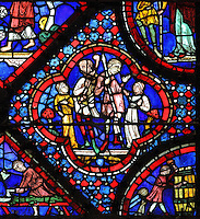 Men talking to giants, from the causes of the flood, from the Life of Noah stained glass window, 13th century, in the nave of Chartres cathedral, Eure-et-Loir, France. Chartres cathedral was built 1194-1250 and is a fine example of Gothic architecture. Most of its windows date from 1205-40 although a few earlier 12th century examples are also intact. It was declared a UNESCO World Heritage Site in 1979. Picture by Manuel Cohen