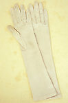Pair of elbow-length white satin ladies gloves slightly grubby through use lying on antique paper