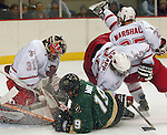 1/28/05  Omaha, NE University of Nebraska at OmahaÕs Dan Knapp and Bryan Marshall get tangled up with Wayne StateÕs John May in front of goalie Chris Holt.  . (photo by Chris Machian/ Prarie Pixel Group)