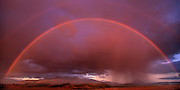906500010 panoramic view of a double rainbow just as the clouds start to break amid a clearing storm right over mount shasta still hidden by cloud cover in the northcentral part of california