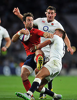 Morgan Parra of France is tackled by Henry Slade of England. QBE International match between England and France on August 15, 2015 at Twickenham Stadium in London, England. Photo by: Patrick Khachfe / Onside Images