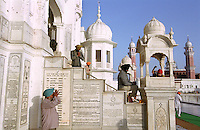Sikh pilgrims pause to pray in front of plaques commemorating Sikh military regiments at the Golden Temple in Amritsar, the holiest of all Sikh shrines.