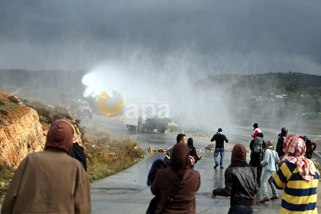 Palestinian youths and Israeli troops clash following a weekly demonstration against Israeli settlement expansion (background), in the West Bank village of Nabi Saleh, on November 18, 2011. Photo by Issam Rimawi