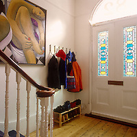 The bright entrance hall of this substantial Victorian house is lit by original stained-glass panels in the front door