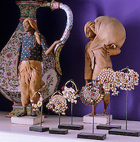 A collection of Indian figurines and nose rings is displayed on a shelf in the living room