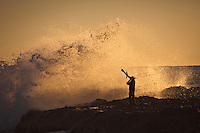 Coolangatta, Queensland. Monday June 3, 2011. A local aboriginal salutes the rising sun and the waves at Snapper Rocks by blowing on his didgeridoo and waving a boomerang. . A  one meter swell continued to hit the Gold Coast today with a light NW wind ruffling the ocean surface.  Photo: joliphotos.com