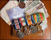 BNPS.co.uk (01202 558833)<br /> Pic: PhilYeomans/BNPS<br /> <br /> Family photos that saved him, Military medal (with bar) as well as the Mons Star, leather wallet, dog tag and his map of the Passchendaele offensive from 1917.<br /> <br /> Saved by pictures of his loving family...<br /> <br /> An amazing tale of a heroes lucky survival through the entire First World War has been uncovered after his family revealed his remarkable tale to a local history group.<br /> <br /> Photos of loved ones that saved a soldier's life by stopping a piece of shrapnel aimed for his heart have come to light - complete with the holes the fragment left behind.<br /> <br /> Private William Taylor kept the nine pictures of his family in his wallet in his breast pocket during the entire four years of World War One.<br /> <br /> In a remarkable quirk of fate he survived a battle which left three quarters of his regiment dead or injured thanks to the stack of photos which took the impact of a shell blast.<br /> <br /> The projectile pierced the outer layer of his leather wallet and perforated eight of the nine photos.<br /> <br /> Luckily, the last picture of his younger sister Lilly stopped the fragment from going any further.