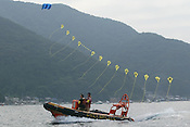 WATCHED BY JAPANESE POLICE ,GREENPEACE SHIP 'ARCTIC SUNRISE' FLIES A KITE READING &quot;STOP PLUTONIUM&quot; AND INFLATABLES PROTEST IN UCHIURA BAY, BESIDE THE TAKAHAMA NUCEAR PLANT, AS BNFL SHIP 'PACIFIC PINTAIL' ARRIVES EARLY MORNING FOR RETRIEVAL OF REJECTED PLUTONIUM MOX FUEL, FOR SHIPMENT BACK TO THE UNITED KINGDOM. TAKAHAMA, JAPAN. 04/07/02. .PIC &copy; JEREMY SUTTON-HIBBERT/GREENPEACE 2002..*****ALL RIGHTS RESERVED. RIGHTS FOR ONWARD TRANSMISSION OF ANY IMAGE OR FILE IS NOT GRANTED OR IMPLIED. CHANGING COPYRIGHT INFORMATION IS ILLEGAL AS SPECIFIED IN THE COPYRIGHT, DESIGN AND PATENTS ACT 1988. THE ARTIST HAS ASSERTED HIS MORAL RIGHTS. *******