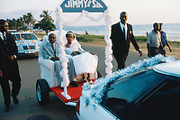 Sierra Leone. Freetown. Aberdeen area. Lumley beach on the atlantic ocean. Wedding of Jimmy B, the most famous musician in Sierra leone. The married couple is seated and is driven in an open vehicle on the road along the beach. Wedding dress.  © 2002 Didier Ruef