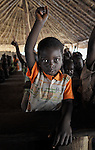 A child raises his hand in a Catholic Church-sponsored school in the Makpandu refugee camp in Southern Sudan, 44 km north of Yambio, where more that 4,000 people took refuge in late 2008 when the Lord's Resistance Army attacked their communities inside the Democratic Republic of the Congo. Attacks by the LRA inside Southern Sudan and in the neighboring DRC and Central African Republic have displaced tens of thousands of people, and many worry the attacks will increase as the government in Khartoum uses the LRA to destabilize Southern Sudan, where people are scheduled to vote on independence in January 2011. Catholic pastoral workers have accompanied the people of this camp from the beginning.