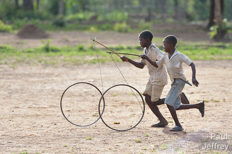 Boys roll bicycle wheels through a camp for for than 5,000 displaced people in Riimenze, in South Sudan's Gbudwe State, what was formerly Western Equatoria. Families here were displaced at the beginning of 2017, as fighting between government soldiers and rebels escalated.<br /> <br /> Two Catholic groups, Caritas Austria and Solidarity with South Sudan, have played key roles in assuring that the displaced families here have food, shelter and water.<br /> The camp formed around the Catholic Church in Riimenze as people fled violence in nearby villages for what they perceived as the safety offered by the church.