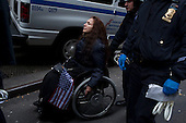 New York, New York<br /> November 17, 2011<br /> <br /> &quot;Occupy Wall Street&quot; protesters mark the movement's two-month milestone by marching from Zuccotti Park, in mass, to various access streets surrounding the New York Stock Exchange, which the police had barricaded off. Yet instead of the police keeping protesters out, protesters locked down those entrances to Wall Street and the New York Stock Exchange creating havoc as the police made more then 240 arrests to try and keep the streets open to normal traffic.<br /> <br /> At Williams and Pine street, NYPD arrest dozens of protesters,  including this woman in a wheelchair. The anti-Wall Street protesters intention to disrupting business as usual on Wall Street was successful.