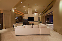 White ectional sofa is placed in fron of free standing fireplace at night