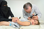 Dr. Saba Ghawi, a pediatrician, examines a young patient in a clinic in Madaba, a sprawling Palestinian refugee camp in Jordan that has grown in recent years with the arrival of refugees from war-torn Syria. The clinic is run by the Department of Service for Palestinian Refugees of the Middle East Council of Churches, a member of the ACT Alliance. <br /> <br /> Parental consent obtained.