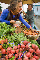 Customer selecting organic carrots and beets a from local grown vegetables at Willow Creek Farms in farmer's market Arcata, California