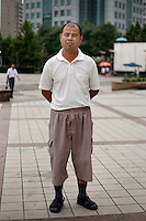 Huangbaoyou, a driver, age 39, poses for a portrait in Beijing. Response to 'What does China mean to you?': 'Home country. '  Response to 'What is China's role in the future?': 'Very developed.'