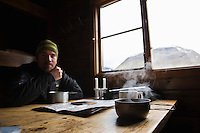 Hot soup steams from titanium camping pan in mountain hut, Kungsleden trail, Sweden