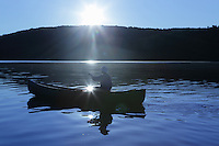 Hortonia, VT, USA - August 23, 2011: Girl paddling canoe across countryside lake in Vermont in the early morning as the sun rises