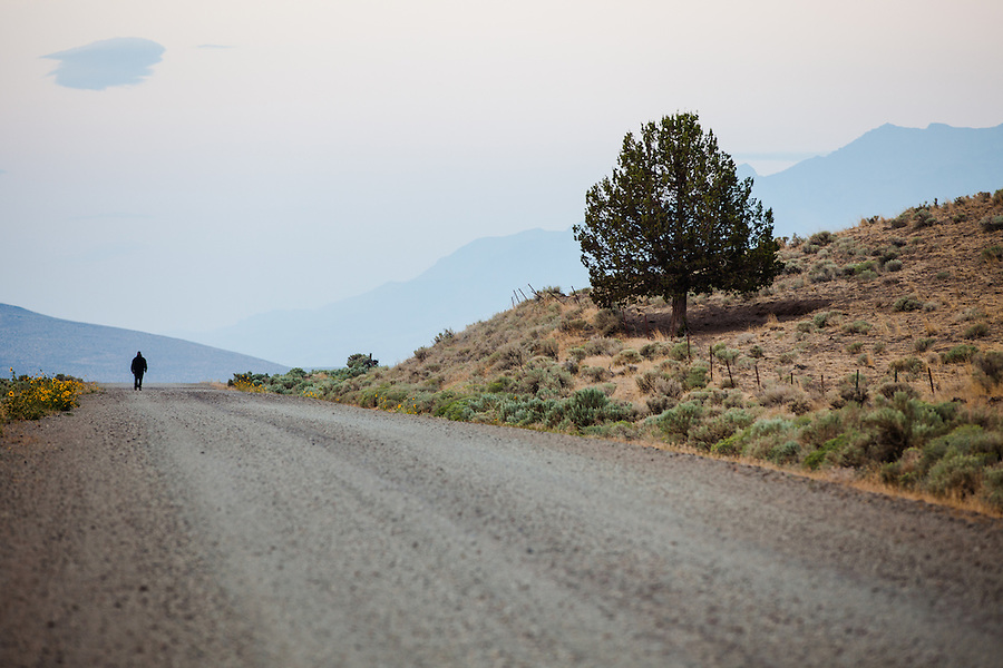 A man walks along the gravel Fields-Denio road in Southeast Oregon past a tree and barbed-wire fence just after dawn.