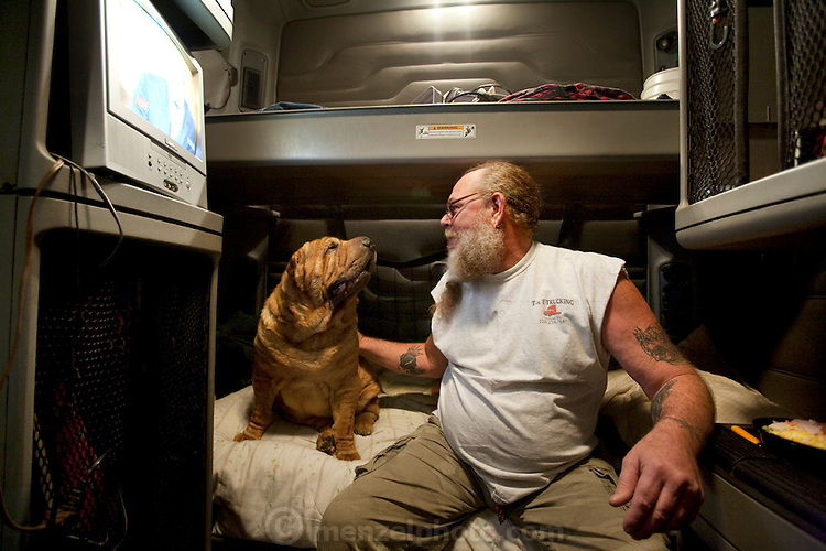 Conrad Tolby, a long-distance truck driver and ex-biker with his best friend and constant companion, Imperial Fancy Pants, a five-year-old shar pei that he travels with. (From the book What I Eat: Around the World in 80 Diets.) The caloric value of his typical day's worth of food in June was 5,400 kcals. He is 54; 6a feet two inches and 260 pounds. ?Those big trucks on the road with all the lights on them? Those are chicken haulers,? says Conrad. ?I used to be on the road 24-7, 300 days a year, hauling fresh-killed chickens packed in ice. I'd leave Mississippi and haul ass to California. You've only got so much time to deliver or you get fined big time.? After two heart attacks, both of them in the cab of his truck, and a divorce back in Mississippi. MODEL RELEASED.